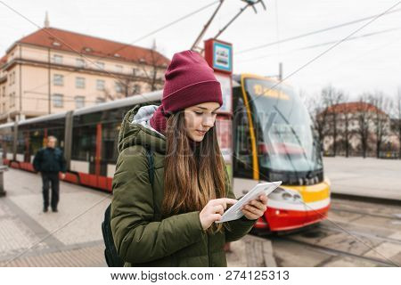 A Girl Or A Tourist Got Off The Tram Stop From A Tram And Looks At A Tablet City Map Or A Mobile App