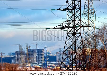 Outskirts of Moscow.In the center of the picture we see the supports of high-voltage power lines, modern houses, roads, construction of buildings. In the foreground-trees without leaves, shrubs. poster
