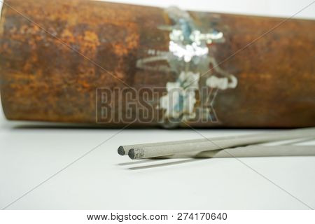 Welding electrode on the background sample of defective weld for testing in a special laboratory at the enterprise poster