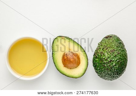 avocado  oil in a small ceramic bowl and avacado fruit against white art canvas