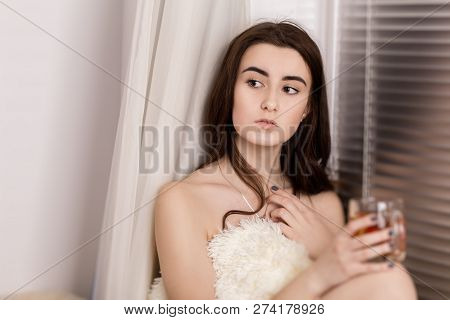 Pensive Young Woman With Cup Of Tea Relax Near Window
