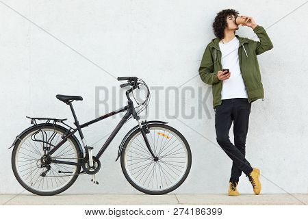 Horizontal Shot Of Fashionable Youngster Keeps Hands Crossed, Holds Mobile Phone, Sends Text Message