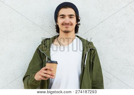 Headshot Of Pleased Hipster Guy Holds Takeaway Coffee, Dressed In White T Shirt And Green Jacket, En