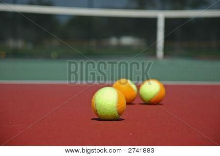 Multi-Colored Tennis Balls On Hard Court