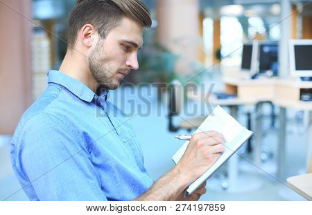 Portrait Of Handsome Smiling Man In Casual Shirt Taking Notes At Workplace.