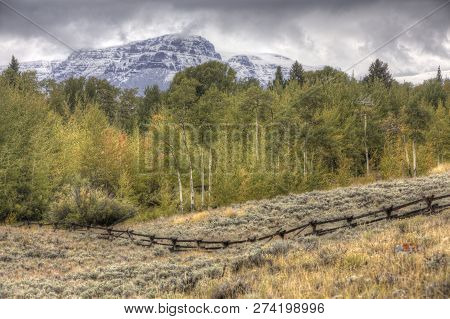 Early Autumn Wyoming Landscape , Snow On Mountains, Wood Fence On Hillside With Sagebrush