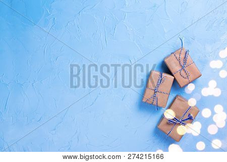Wrapped Boxes With Presents With Bokeh Lights  On Blue Textured Background. Top View.  Flat Lay. Win