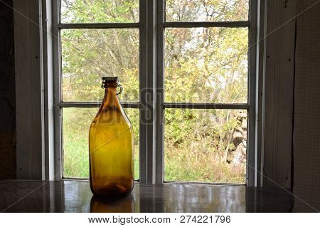 Interior Decoration With An Old Brown Bottle By A Window With Green Garden Outdoors