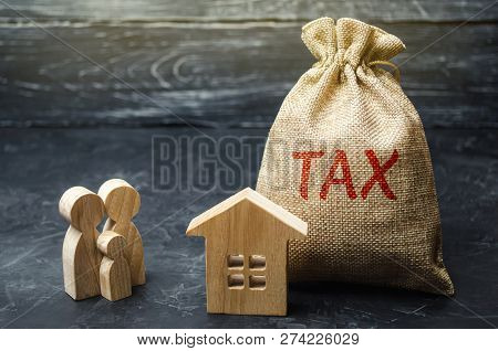 A Bag With The Word Tax And Family Stand Near The House. Taxes On Real Estate, Payment. Penalty, Arr