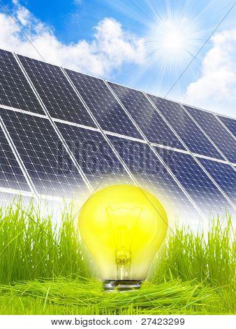 Lamp bulb and solar panels in fresh spring grass. Conceptual image. Environmental metaphor.