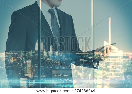 Young Businessman Using Smartphone On Blurry Night City Background. Communication And Lifestyle Conc