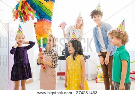 Serious Curious Girl In Denim Suit Holding Bat And Looking At Upside Down House Pinata While Prepari