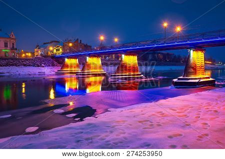 Uzhgorod, Ukraine - Dec 26, 2016: Pedestrian Bridge Through The River Uzh At Night. Beautiful Citysc