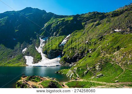 Lake Balea Of Fagaras Mountains. Last Pieces Of Snow On The Grassy Hills. Beauty Of Romania