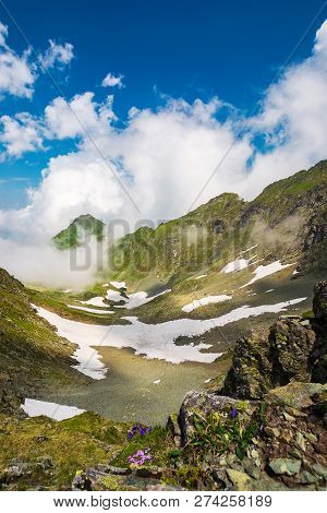 Wonderful Springtime Scenery In Mountains. Rocky Slope With Green Grass And Spots Of Snow. Clouds Ri