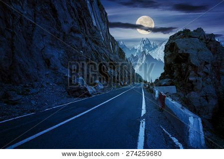 Road In To The High Mountains Between Rocky Cliff At Night In Full Moon Light. Composite Image Of Da