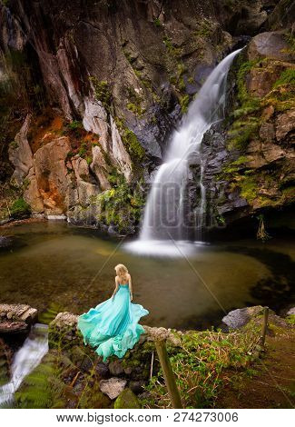 Beautiful Blonde Woman In Elegant Turquoise Long Dress Under A Waterfall Outdoor.