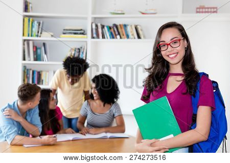 Nerdy Female Student With Eyeglasses And Group Of International Students At Library Of University