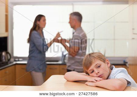 Sad little boy hearing his parents arguing in a kitchen