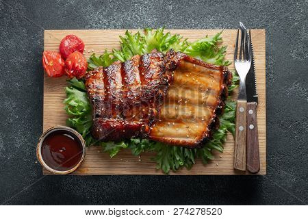 Closeup Of Pork Ribs Grilled With Bbq Sauce And Caramelized In Honey On A Bed Of Salad Frisse. Tasty