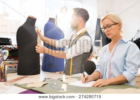 Portrait of fashion designers working in atelier lit by sunlight, focus on mature woman drawing sketches in foreground, copy space poster