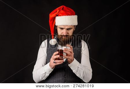 Business Man In Santa Hat Holds Glass Of Whiskey. Santa Man Tasting Glass Of Whisky. New Year Party.