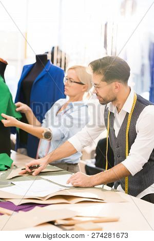 Portrait of two modern fashion designers making clothes while working in atelier workshop poster