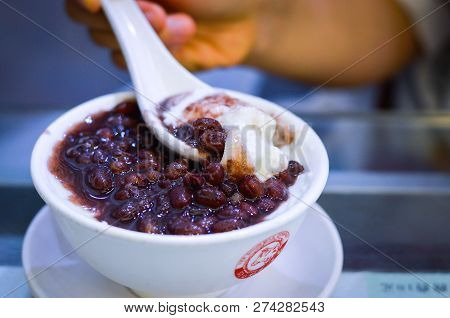 Hong Kong, August, 2018. Hand Spoons Up Red Bean Double Skin Milk Pudding From A White Bowl With Yee