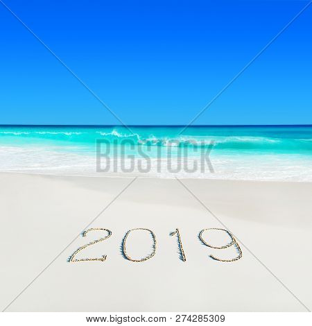 Turquoise Ocean Water At Tropical White Sandy Beach And Season 2019 Handwritten Caption On Sand. Tro
