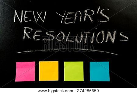 New Year Resolutions Written With Chalk On Blackboard With Blank Colorful Post Its Memo Notes