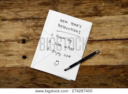 2019 New Year Resolutions List Written On Notebook And Happy Face On Wood Table In Better Life Goals