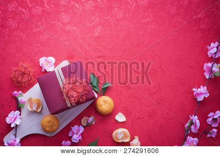 Gift Box And Cherry Blossom With Copy Space For Text On Red Texture Background, Concept Of Chinese N