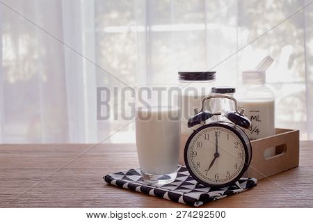 Wood Table With Glass Of Milk And Retro Alarm Clock In Living Room. Front View Table.
