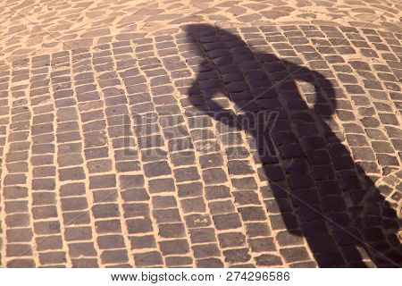Strange Shadow Of A Woman On An Old Stone Road. Black Shadow, Female Hand. Background, Texture, Crop