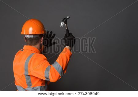 Builder Is Hammering A Nail Into A Wall By A Hammer In His Hand Isolated On Gray Background With Cop