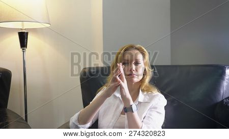 Close-up. An Elegant Woman In A White Suit Sits In A Large Black Leather Chair, Looks Into The Camer