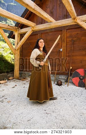 Gudvangen, Norway - June 13 - The Young Woman In National Clothes With Sword In The Viking Village M