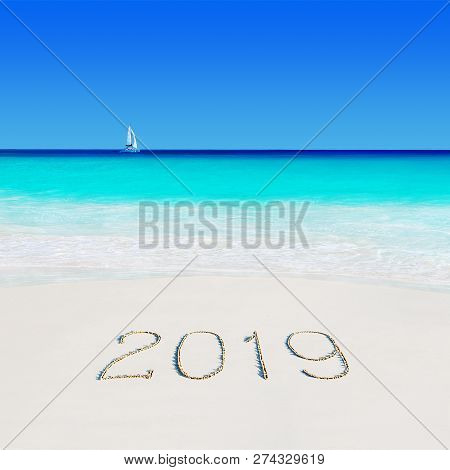 Yacht Under Sail In Ocean Water At Tropical Beach And Happy New Year 2019 Season Caption On Sand. Tr