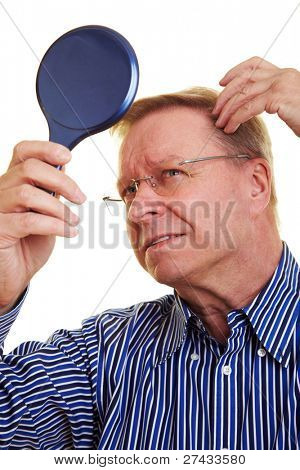 Elderly man watching his receding hair line in mirror