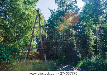 Power Lines In Glade Along Trees. Pole With Wires Near Dirt Road Among Pines And Birches In Sunlight