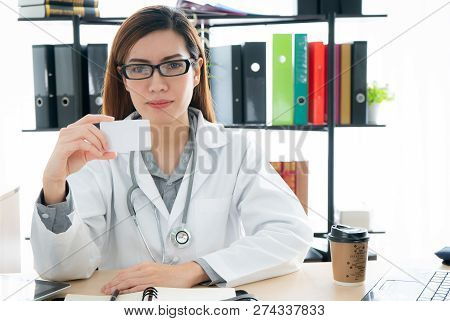 Smiling Female Doctor Sitting In Office And Showing White Blank Card