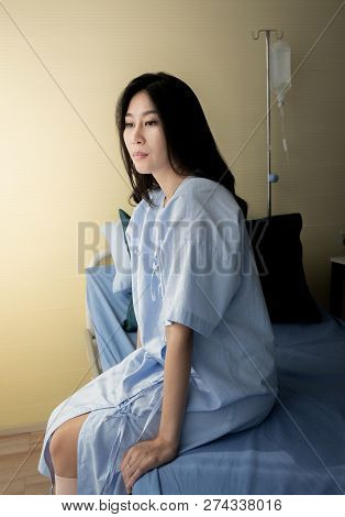Female Patient Sitting On Bed In Hospital
