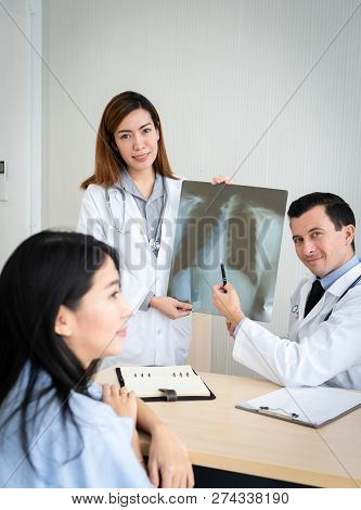 Team Of Doctor Explain About X-ray Result To Female Patient In Hospital