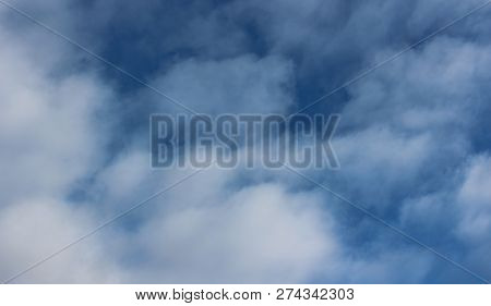 Conceptual background image of bright blue skies and big puffy cloud cover. poster