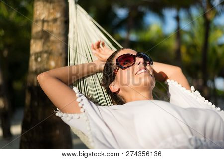 Tranquil Woman Relaxing Lying On A Hammock At Tropical Beach. Summer Vacation Relax And Tranquility