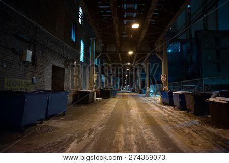 Dark and eerie urban city winter alley under a vintage railway bridge at night