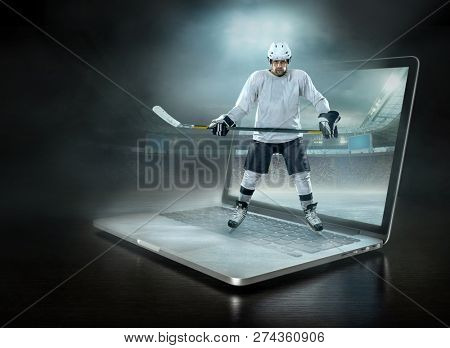 Caucassian ice hockey Player stay in a professional sport game play on the laptop in hockey under stadium lights.