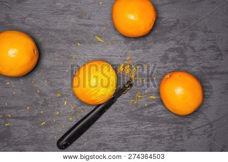 Scraping orange zest with a peeler. recipe step by step hot red mulled wine flatlay on grey stone poster