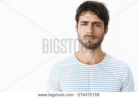 Guy Looking Frustrated And Disappointed Squinting Feeling Doubtful, Unsure And Suspicious Standing C