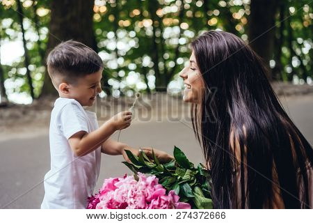 Happy Mother With Her Young Son In A Summer Park.